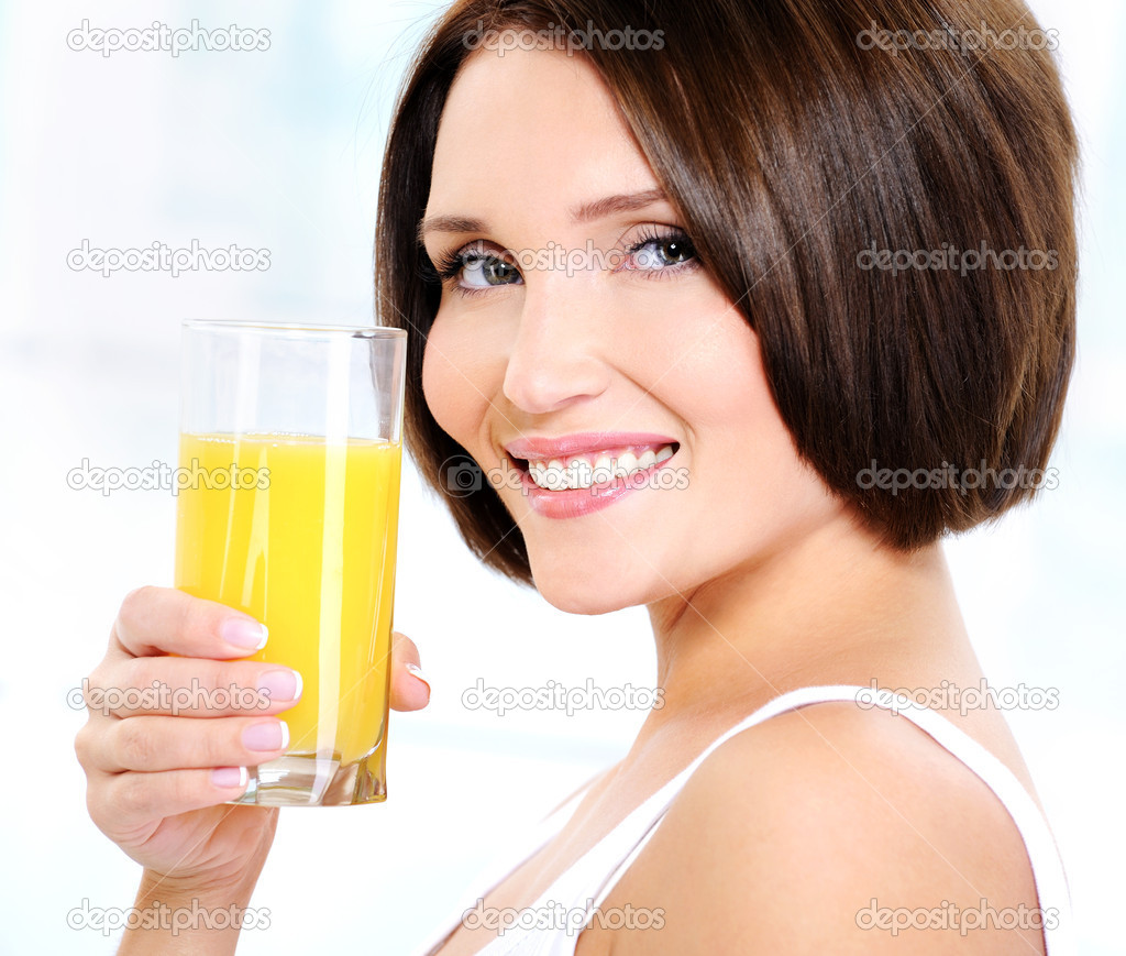 Young beautiful smiling woman holding glass of orange juice  Stock Photo #1513086
