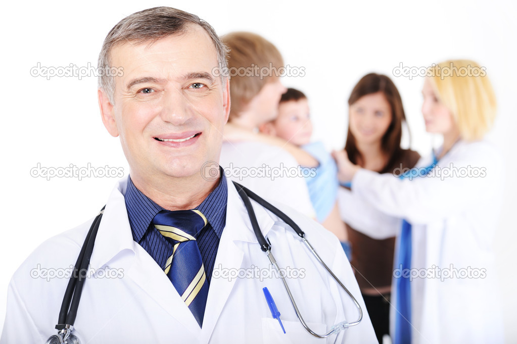 Portrait of smiling successful mature male doctor in the foreground and the young family — Stock Photo #1514618