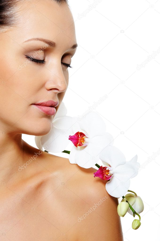 Portrait of beautiful woman in profile with a white orchid flower on her shoulder over white background  Stock Photo #1519370