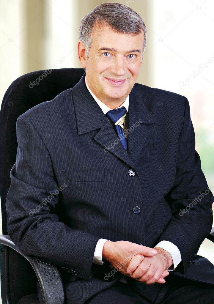 Portrait of middle aged senior business sat in chair smiling with hands folded on lap. — Stock Photo #1520077
