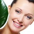 Green leaf near the face of woman — Stock Photo #1534967
