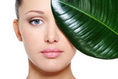 Green leaf shading a female face — Stock Photo