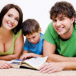 Preschool boy reading book with  parents - Stock Photo