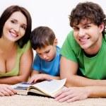 niño preescolar lectura con padres — Foto de Stock