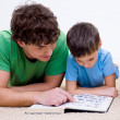Father and son indoors reading book — Stockfoto