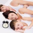 Family sleeping with alarm clock — Stock fotografie