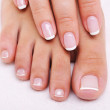 Beauty nails of a female hand and feet — Stock Photo