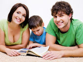 Pré-escolar menino lendo um livro com os pais — Fotografia Stock