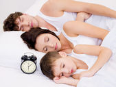 Family sleeping with alarm clock — ストック写真