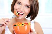 Cheerful female eats vegetable salad — Stock Photo