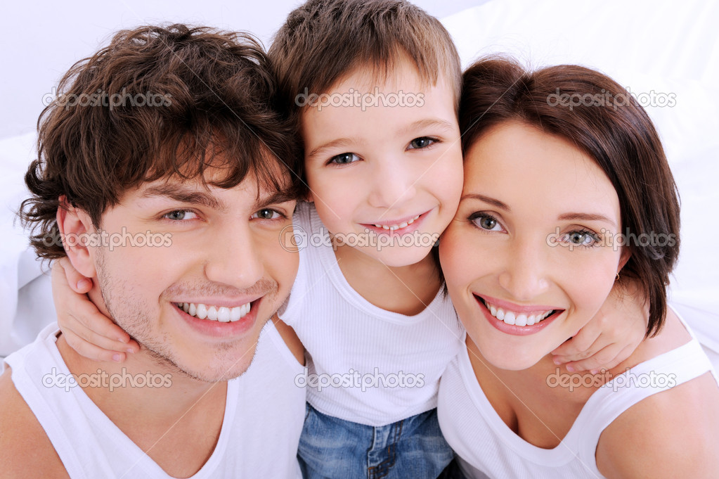 Beautiful smiling faces of  . A happy young family from three persons  Stock Photo #1547726