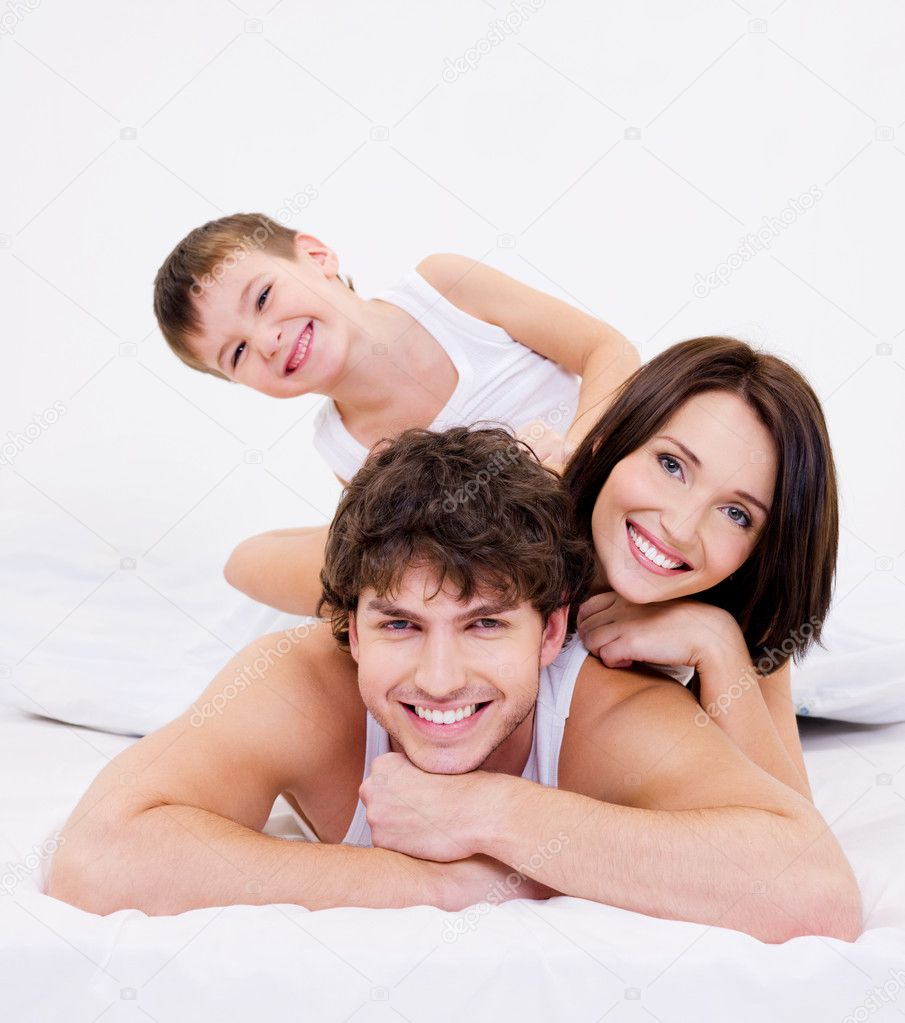 Faces of the Happy and fun  family lying in bed — Stok fotoğraf #1547831