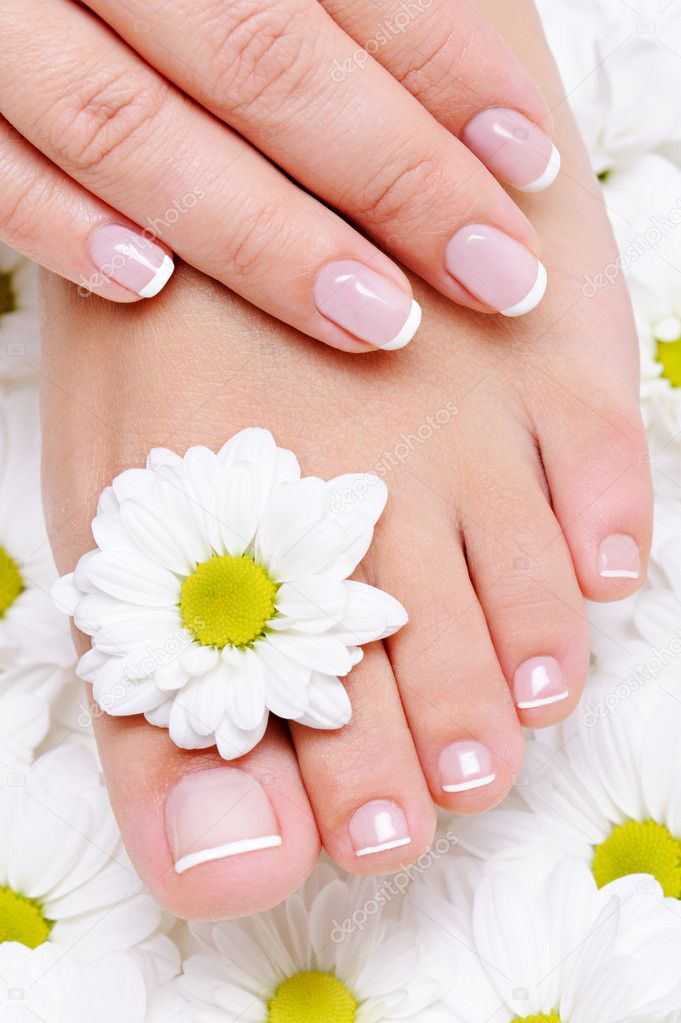Female hand with beautiful french manicure on the pure and clean foot — Stock Photo #1549803