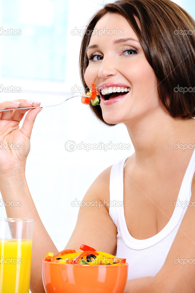 The beautiful laughing young woman the vegetarian eats useful vegetable food — Stock Photo #1549973
