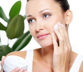Woman applying moisturizer cream — Stock Photo