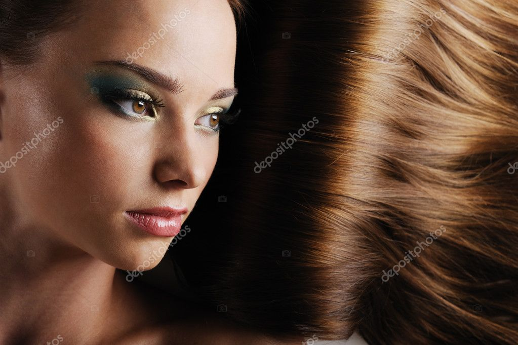 Close-up beautiful female face with luxuriant long hair as a background — Stok fotoğraf #1550240