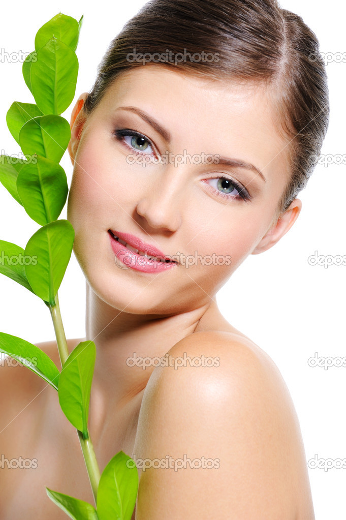 Beautiful smiling female face with a clean healthy skin and plant near her body — Stock Photo #1553047