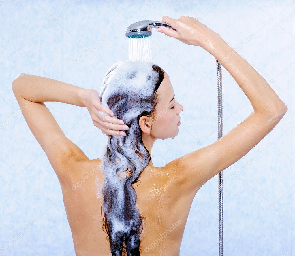 Pretty female standing back and washing her long hair — Stock Photo #1553060
