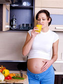Pregnant woman drinks orange juice — Stock Photo