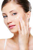 Female applying cosmetic cream on skin — Stock Photo