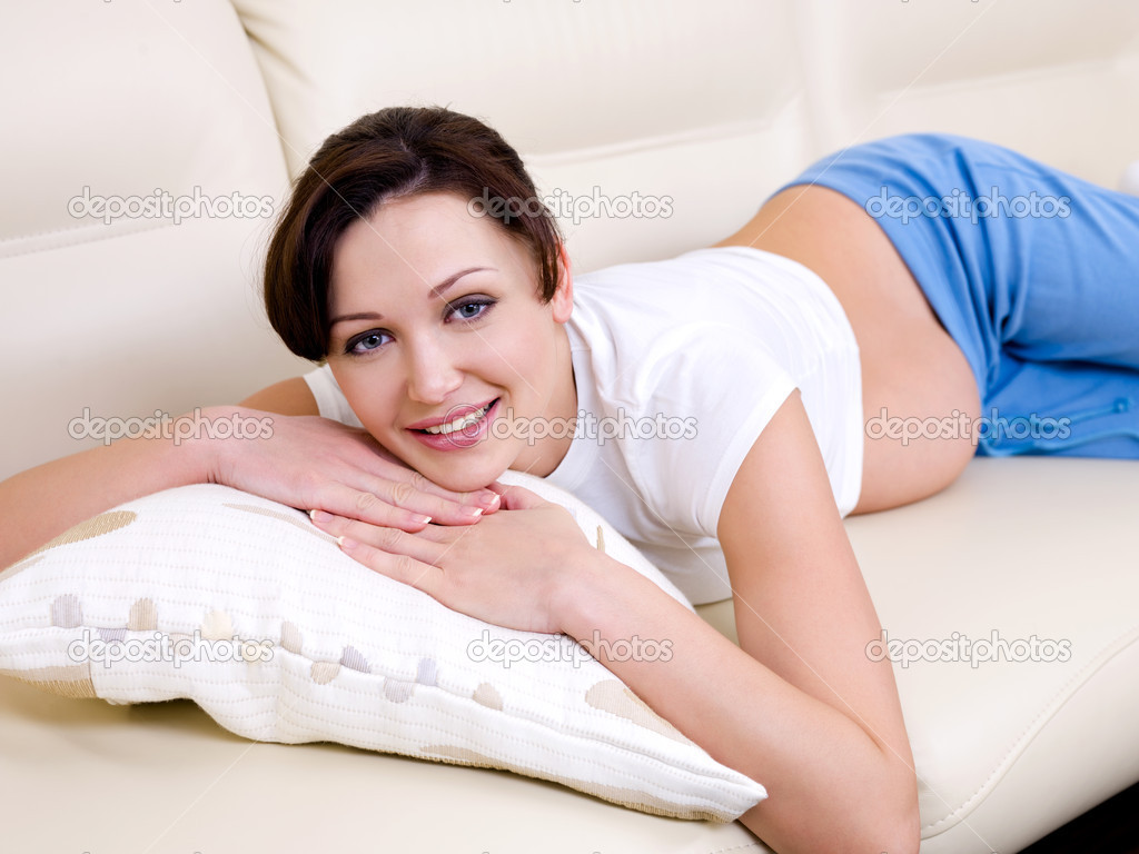 Beautiful cheerful pregnant woman lying on the sofa  Stock Photo #1591149