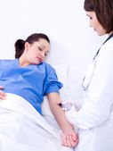 Doctor takes blood at pregnant woman — Stock Photo