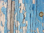Checked and peeling blue paint on wood — Stock Photo