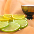Stock Photo: Lemon and lime with cup of teand p