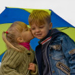 Stock Photo: Little boy and girl with umbrella