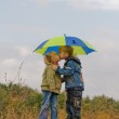 Little boy and girl with umbrella — Stock Photo
