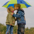 Little boy and girl with umbrella — Stock Photo #1425902