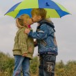 Little boy and girl with umbrella - Stock Photo