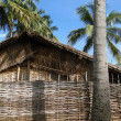 Stock Photo: Thatched huts and palm trees