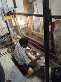 Young muslim man runs a loom to weave silk broca — Stock Photo