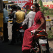 Indian woman in saree sits side saddle on a mot — Stok fotoğraf