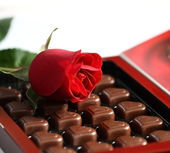 Box of assorted chocolates and rose — Stock Photo