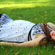 Pregnant woman relaxing in the park - Stock Photo
