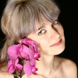 Beautiful woman and orchid near the face - Stock Photo