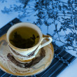 Photo: Green tea in a cup with a tea leafs