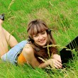 Stock Photo: Smiling young girl with laptop on grass