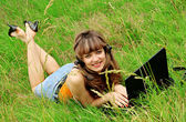 Smiling young girl with laptop on grass — Stock Photo
