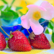 Three Strawberries lying at plate with checkered — Stock Photo