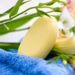 Soap and flower on blue fabric background — Stock Photo