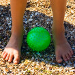 Child Feet on sand at green ball — ストック写真
