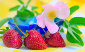 Three Strawberries lying at plate with checkered — Foto Stock