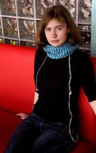 Girl in Blue Scarf Sitting on Red Sofa — Stock Photo