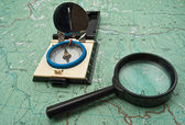 Map, compass and magnifying glass — Stock Photo