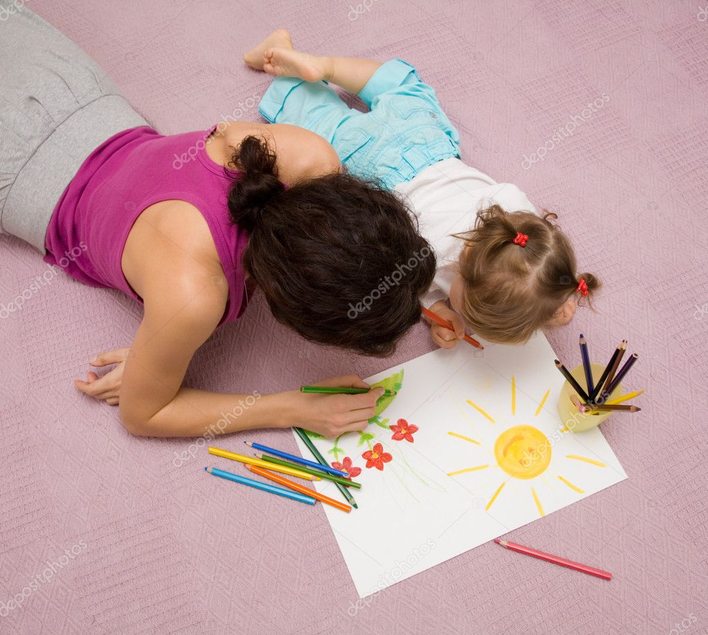 Beautiful mother draws with a small daughter lying on a floor  Stock Photo #1763628