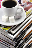Cup of coffee on a pile of magazines. — Stock Photo
