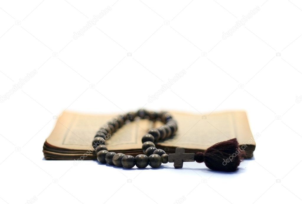 A rosary on antique gospel. Focus accent on the cross. — Stock Photo #1450783